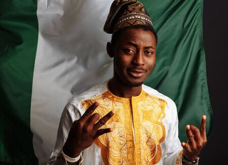 African man with traditional clothes is posing before the camera, smiling and has fun. Before the flag of nigeria