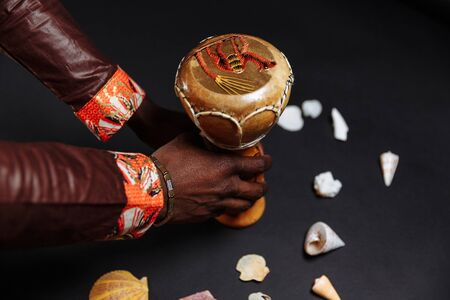 Hands of an African man in national clothes holds djembe drum surrounded by seashells