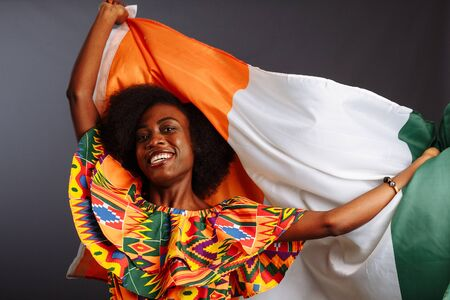 Happy african woman in national clothes smiling and posing with a flag Ivory Coast, C te dIvoire isolated over a gray background 写真素材