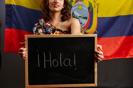 Portrait of young Latin American woman student holding a chalkboard with Hello word on her native language before the Ecuadorian flag..