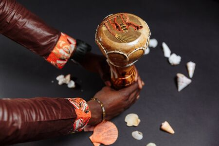 Hands of an African man in national clothes holds djembe drum surrounded by seashells..