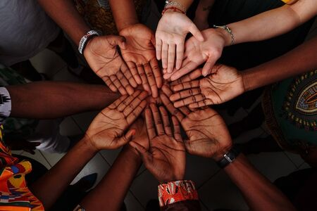 Palms up hands of happy group of multinational African, latin american and european people which stay together in circle.. 写真素材