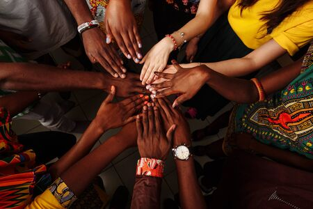 Hands of happy group of multinational African, latin american and european people which stay together in circle..