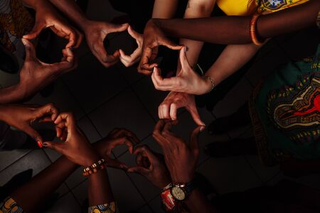 Hands in the form of heart of happy group of multinational African, latin american and european people which stay together in circle 写真素材