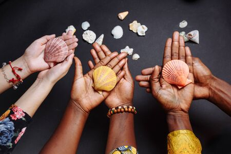 Hands of African people in traditional clothes holding seashells 写真素材