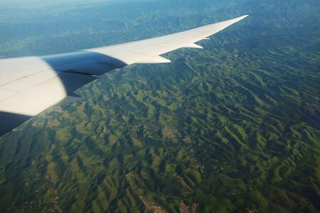 The trees under the wing of the plane during the landing. View through the illuminator.. 写真素材