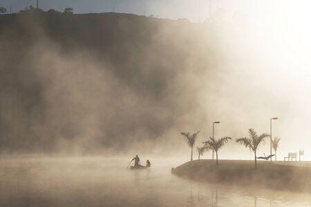 Fisherman on a boat Sunrise and mist fog in the beautiful lake..