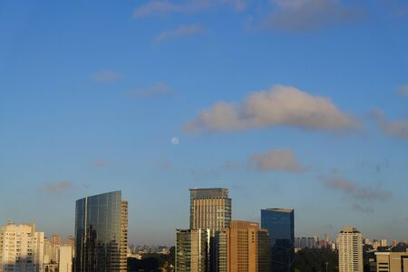Flat cityscape with blue sky, white clouds and moon. Modern city skyline flat panoramic background. Urban city tower skyline illustration.. 写真素材