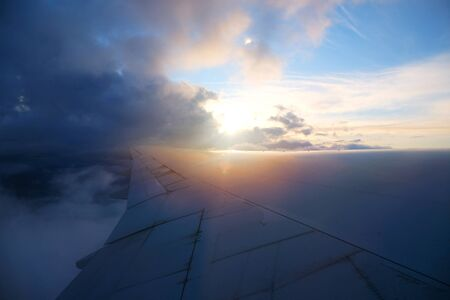 View from airplane window with sky and white clouds at the sunset..
