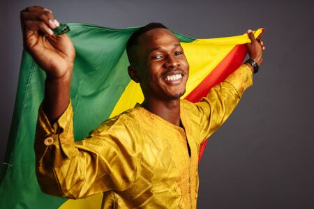 Young man in gold national clothes smiling into the camera and posing with Congo Flag isolated in gray Background.