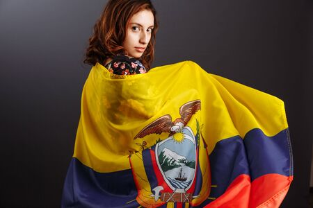 Happy Ecuadorian woman smiling and posing with a flag - isolated over a gray background