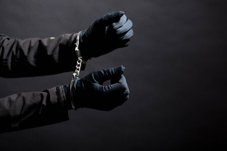 closeup of the hands of a burglar in black gloves with handcuffs on a black background.