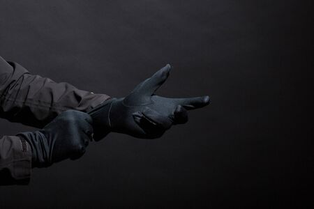Hand in black gloves of a crime on a black background. Gloves are worn on the hand. The man puts a black glove on his hand..