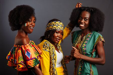 Three young beautiful African fashion models have fun and laughing in traditional dress. Women from the Congo Republic, Ivory Coast, and Zimbabwe