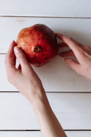 hand holding pomegranate on the white wooden table. Imagens
