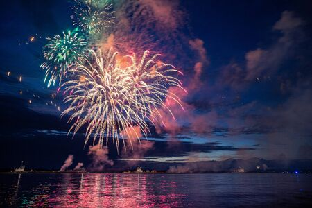 Colorful fireworks reflect from water, beautiful scenery.