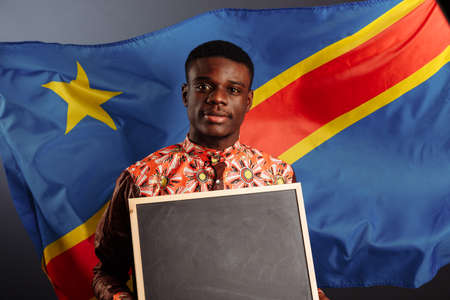 African man in a national clothes of Congo holding a small empty blackboard, place for text and captions 版權商用圖片