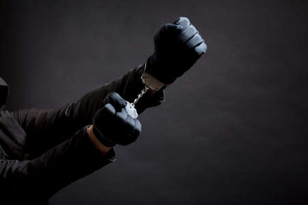 closeup of the hands of a burglar in black gloves with handcuffs on a black background