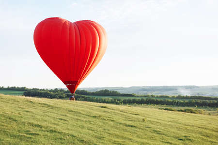 Hot air balloon in the shape of a heart is landing on the green valley. Standard-Bild
