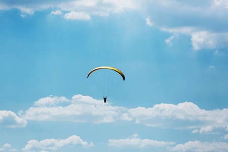 Yellow Paraglider flying into the sky with clouds on a sunny day