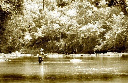 Infrared and sepia toned fly fishing in trout river