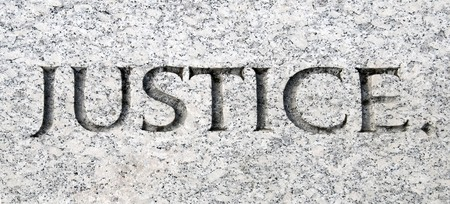 fair trial: The word justice carved in stone Stock Photo