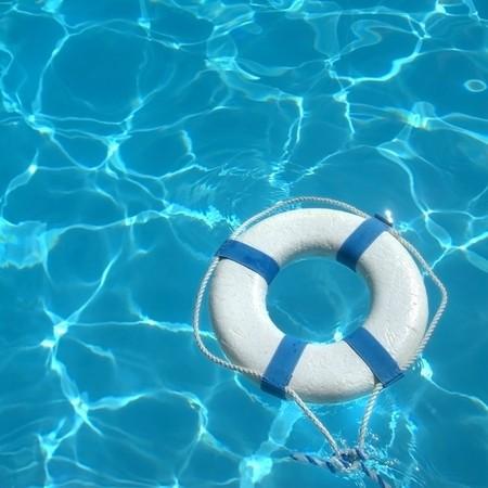 Anello di vita galleggiante sulla cima di sole blu acqua Archivio Fotografico - 7400133
