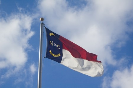 The North Carolina State flag flying on a sunny day photo