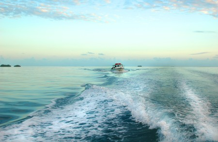 Boat driving in another boats wake, beautiful tropical sunset photo