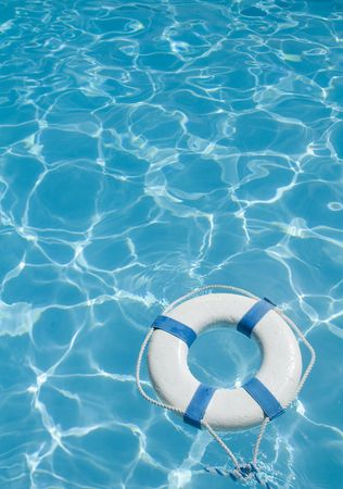 Life ring floating on top of sunny blue water Stock Photo
