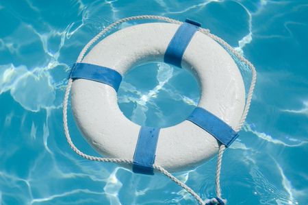 Closeup of a life preserver ring floating on beautiful blue water Archivio Fotografico