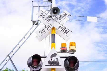 railway sign and traffic lights at a railroad crossing in Thai photo
