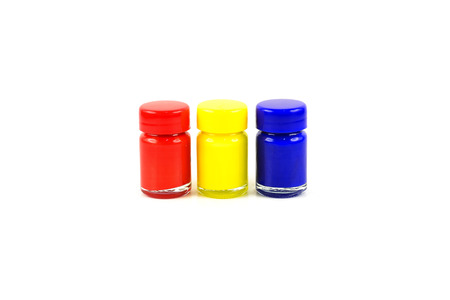 Bottles of primary color on white background photo
