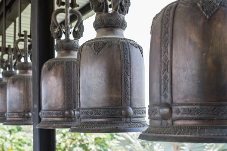 steel beam: Large black bell hanging in rows on a steel beam,Nongnuch garden thailand Stock Photo