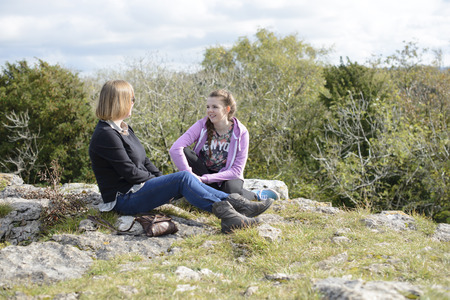 Mother and teenage daughter sitting down chatting and smiling during a hillside walk relaxing together. Outdoors lifestyle.