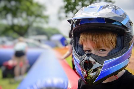 Young boy wearing motorcycle helmet at a county fairground waiting to go on a quad bike. Safety concept