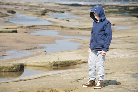 Young boy in blue jacket standing on rocks and exploring  at the seaside. Taken in Whitley Bay in the North East of the UK