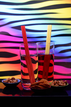 2 drinks with straws and selection of nibbles against a multicolored background