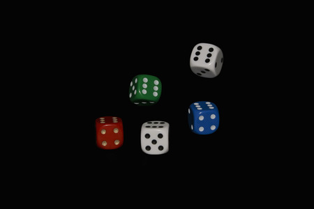 Tumbling dice isolated against a black background