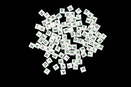 word game: Landscape image of white word game tiles with green lettering on a black background