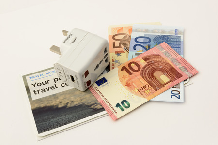 International travel plug and Euro notes isolated on a white background