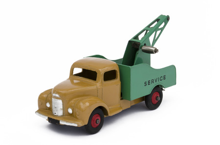 Vintage toy towing truck. Isolated against a white background