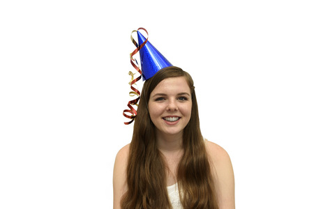 Party Girl. Smiling, young woman wearing a blue party hat with red and gold streamers isolated on a white background
