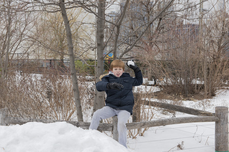 Young boy sitting on a wooden fence preparing to throw a snowball