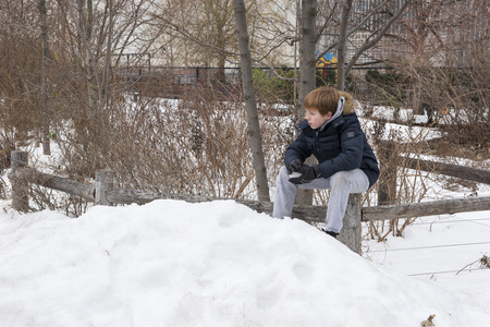 Young boy sitting on a wooden fence holding a snowball Stock Photo