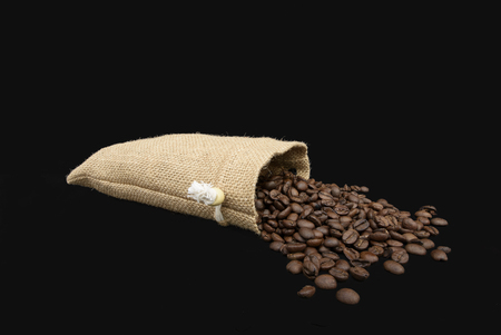 Coffee Beans spilling out of a burlap sack. Isolated against a black background