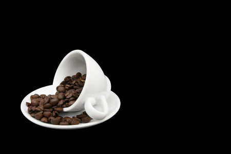 White coffee cup on its side in a saucer with spilt coffee beans. Isolated on black. Copy space
