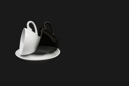 Pair of coffee cups (one black and one white) lying on their side on a white saucer. Isolated on a black background. Copy space.