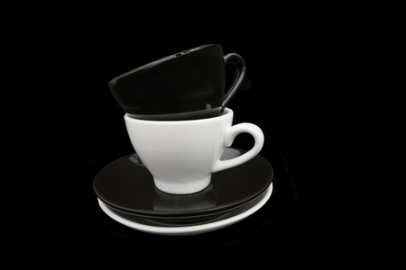 Two stacked black and white coffee cups and saucers. Isolated on a black background