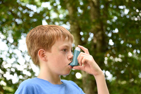 Young boy using a blue asthma inhaler